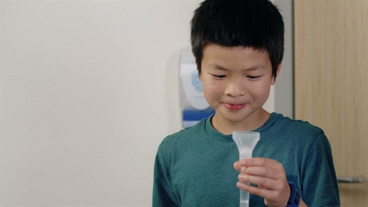 Child with mouth rinse and gargle test container