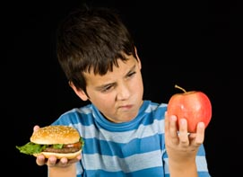 Food and Your Health: boy choosing btween hamburger and apple